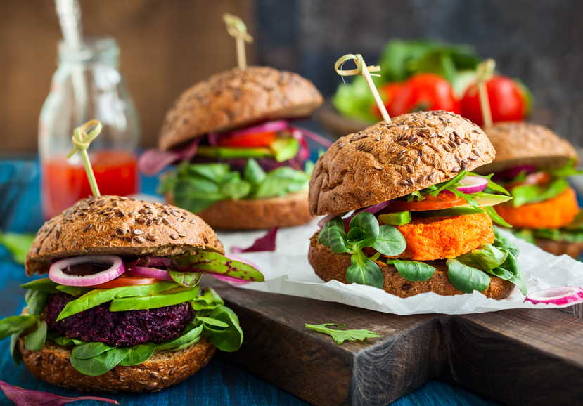 Four thick veggie beet, carrot and avocado burgers on rolls