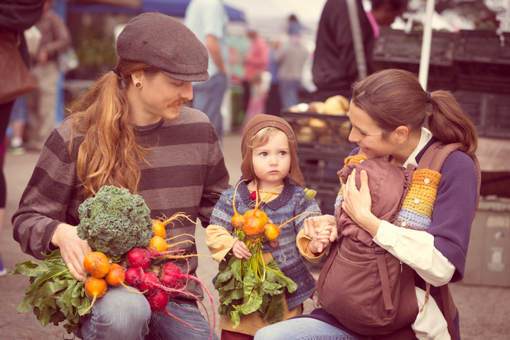 Young Hipster family with produce from outdoor farmers market
